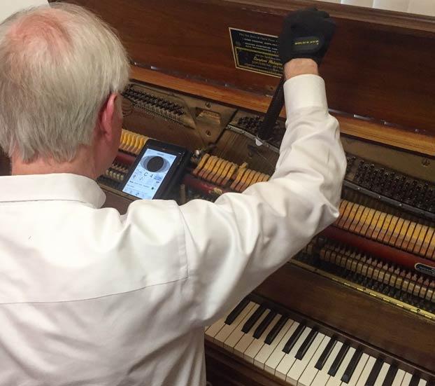 man tuning a upright piano